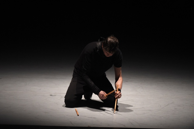 Image of percussionist kneeling with three drums sticks